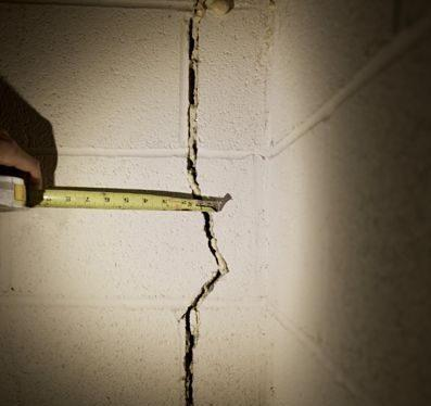 person measuring crack in concrete wall