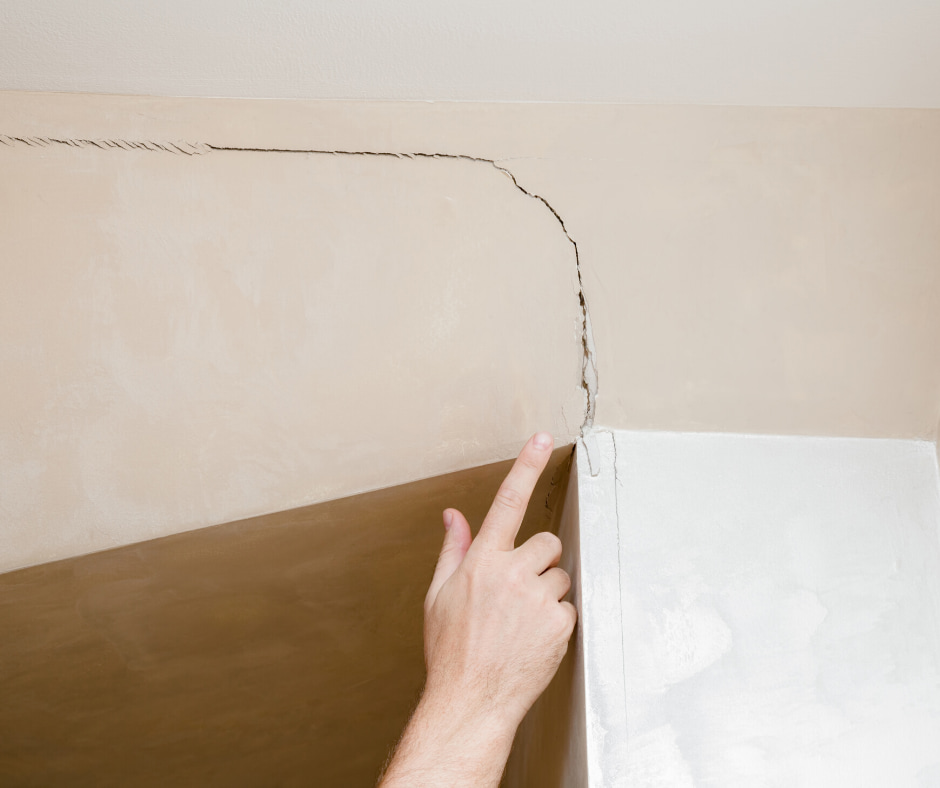 Cracked drywall and a person pointing at it