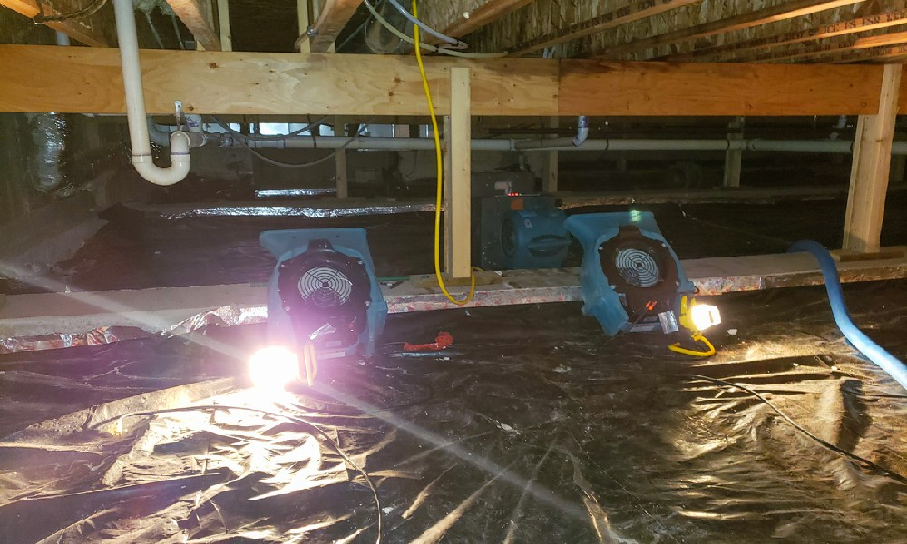 a water-damaged crawl space under repair with equipment and lights