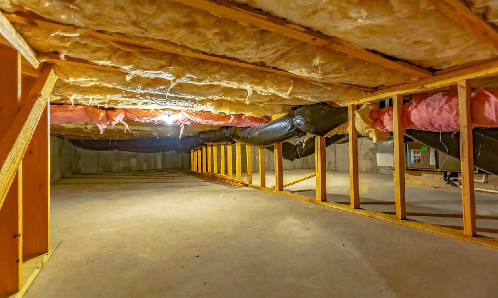 A wide, clean crawl space with visible support beams, insulated pipes, and floors demonstrates the benefits of sealing a crawl space.