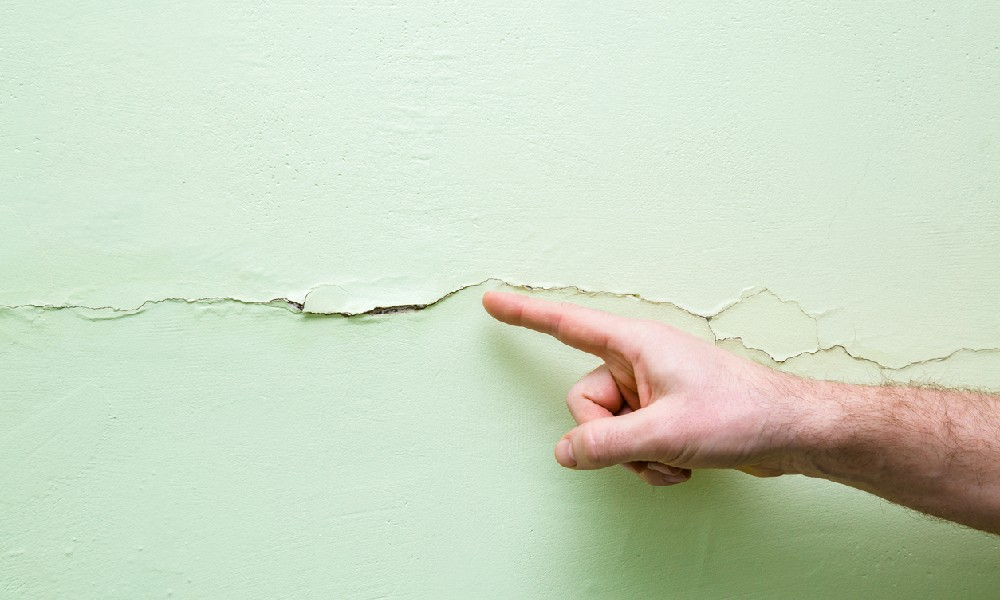 A man's finger points to a horizontal crack in a wall