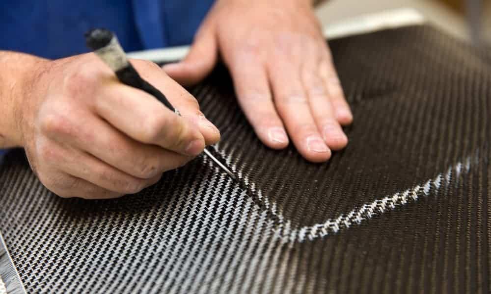 someone cutting a piece of carbon fiber