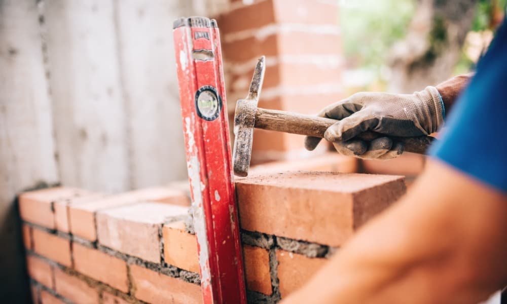builder working with a spirit level and hammer on brick mortar repair