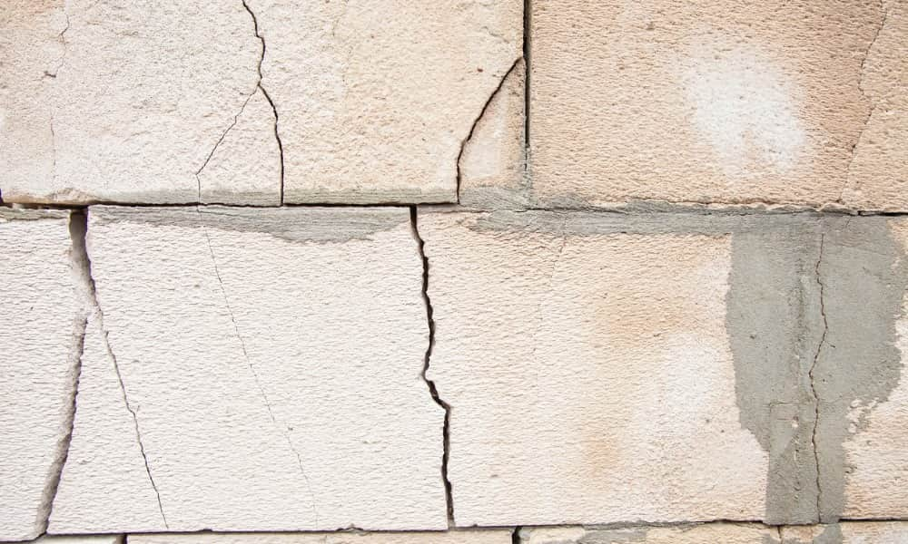 a cracked brick wall shows the need for helical piers to repair an unstable foundation.