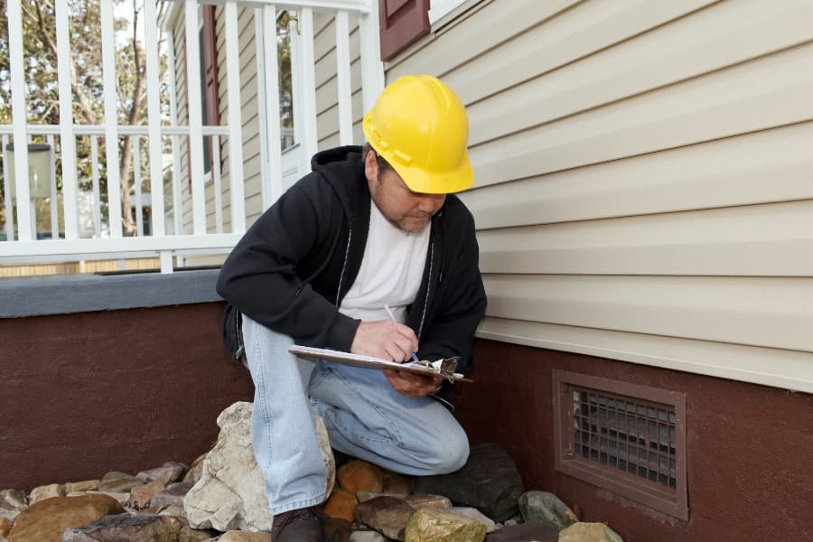 a man performing a foundation inspection on a home